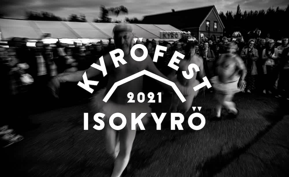 A black and white picture of a Kyröfest, blurry focus on farmers dressed up in tutu skirts with the