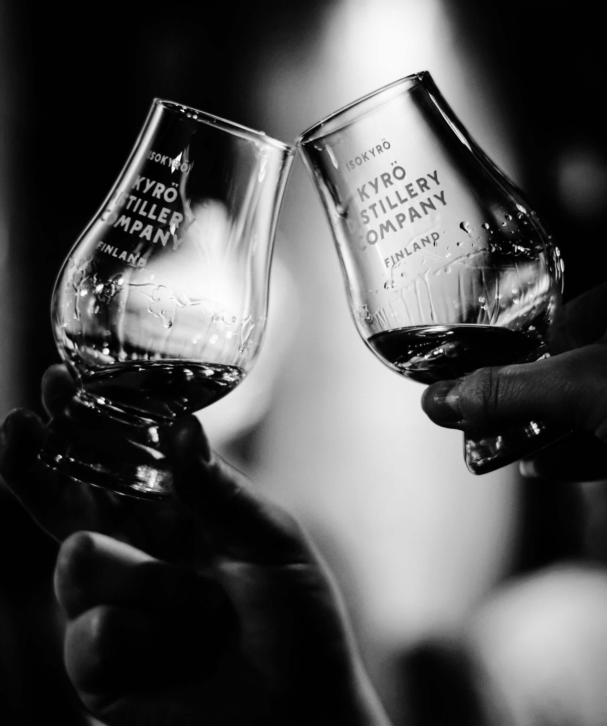 Black and white image of two Kyrö-branded Glencairn tasting glasses filled with whisky cheersing each other.