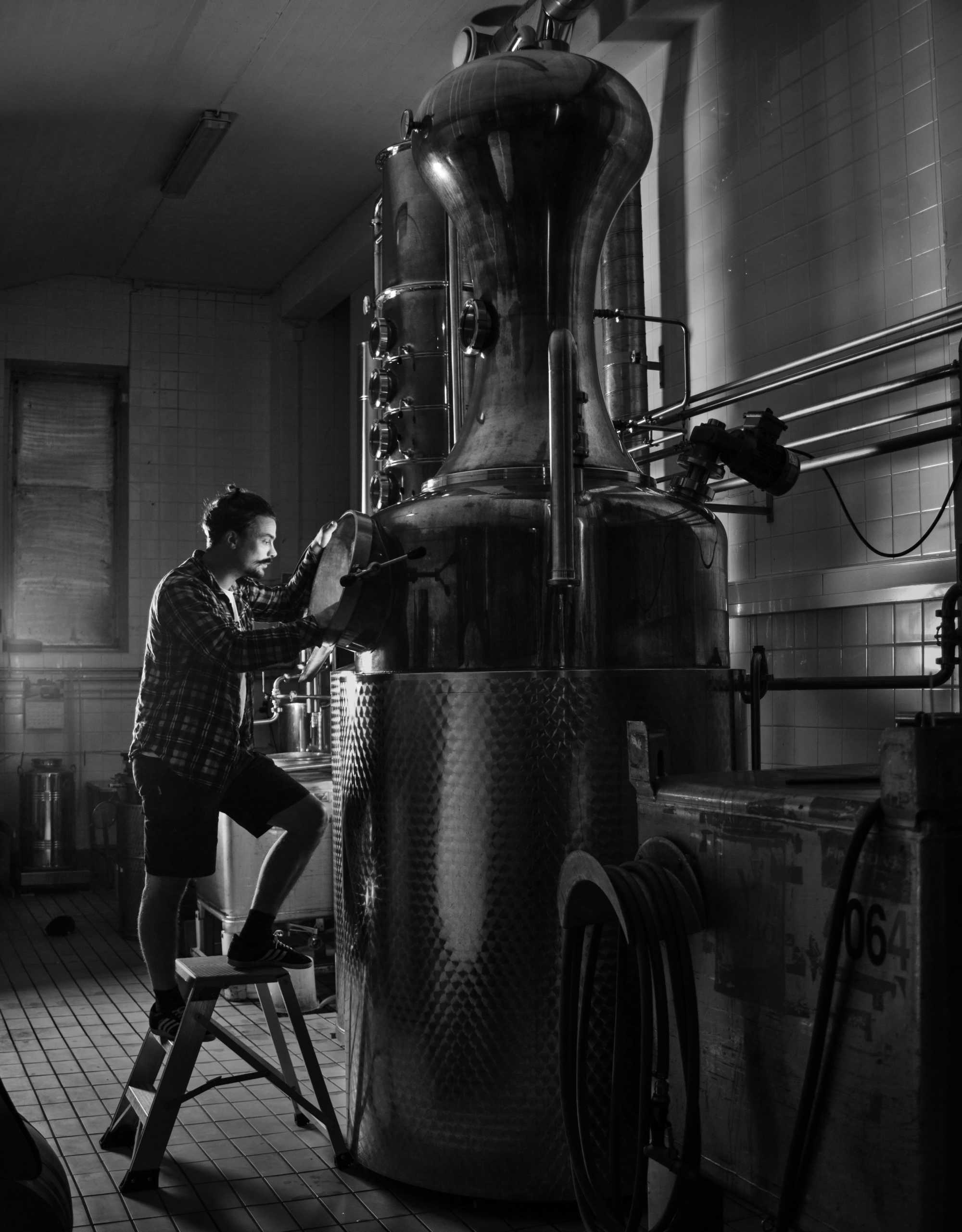 Black and white image of head distiller Kalle Vallkonnen standing on a ladder, peering into a distilling pot.