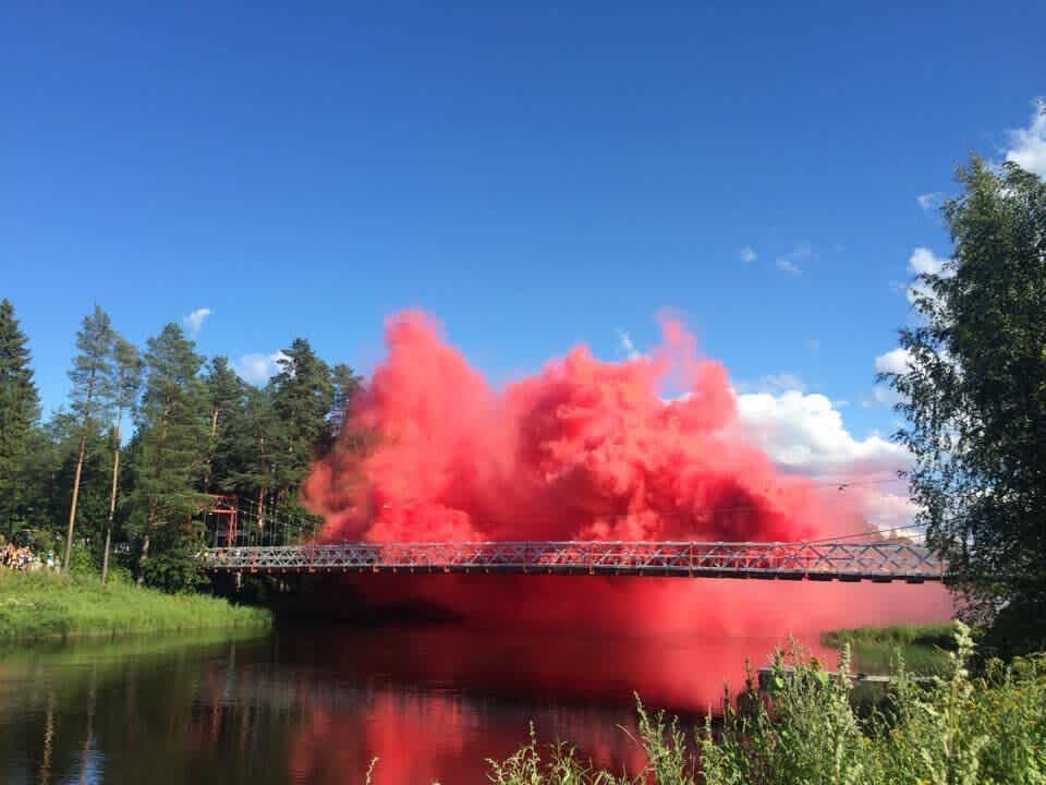 Image of a pink cloud exploding on top of a bridge surrounded by forest and greens.
