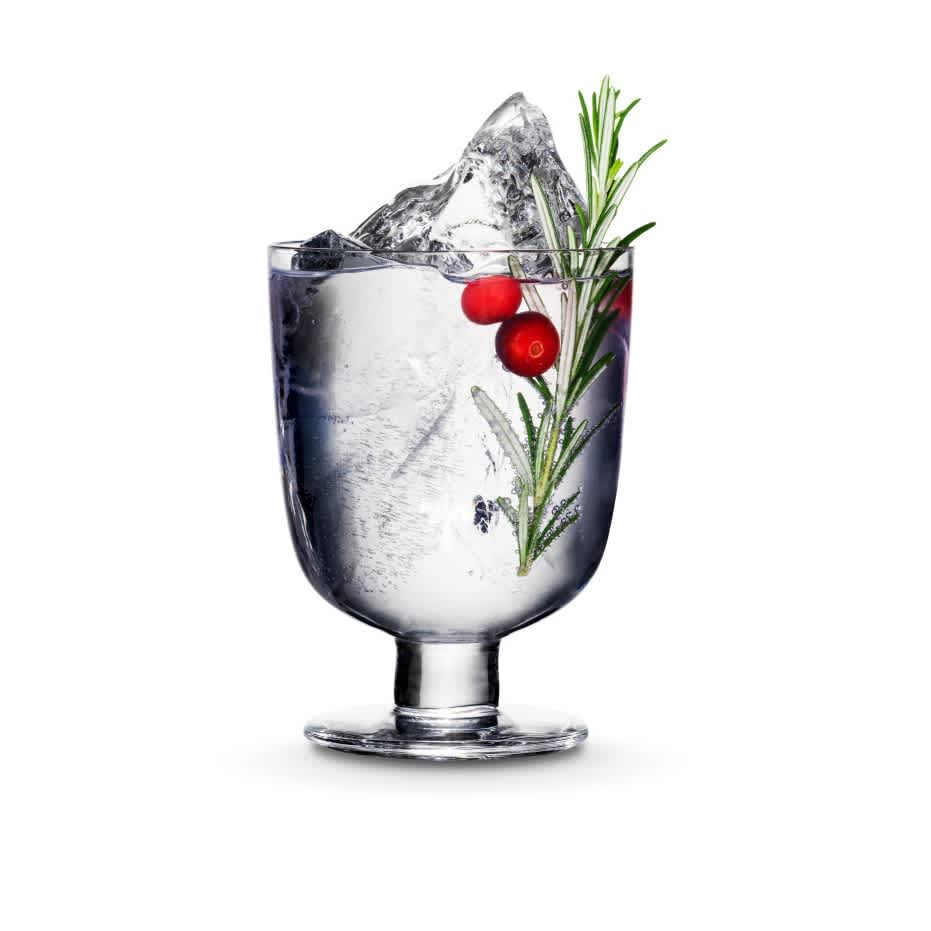Kyrö Gin served in an Iittala cocktail glass with a shard of hand-cut ice, cranberries, rosemary, and Fever-Tree Indian tonic water.