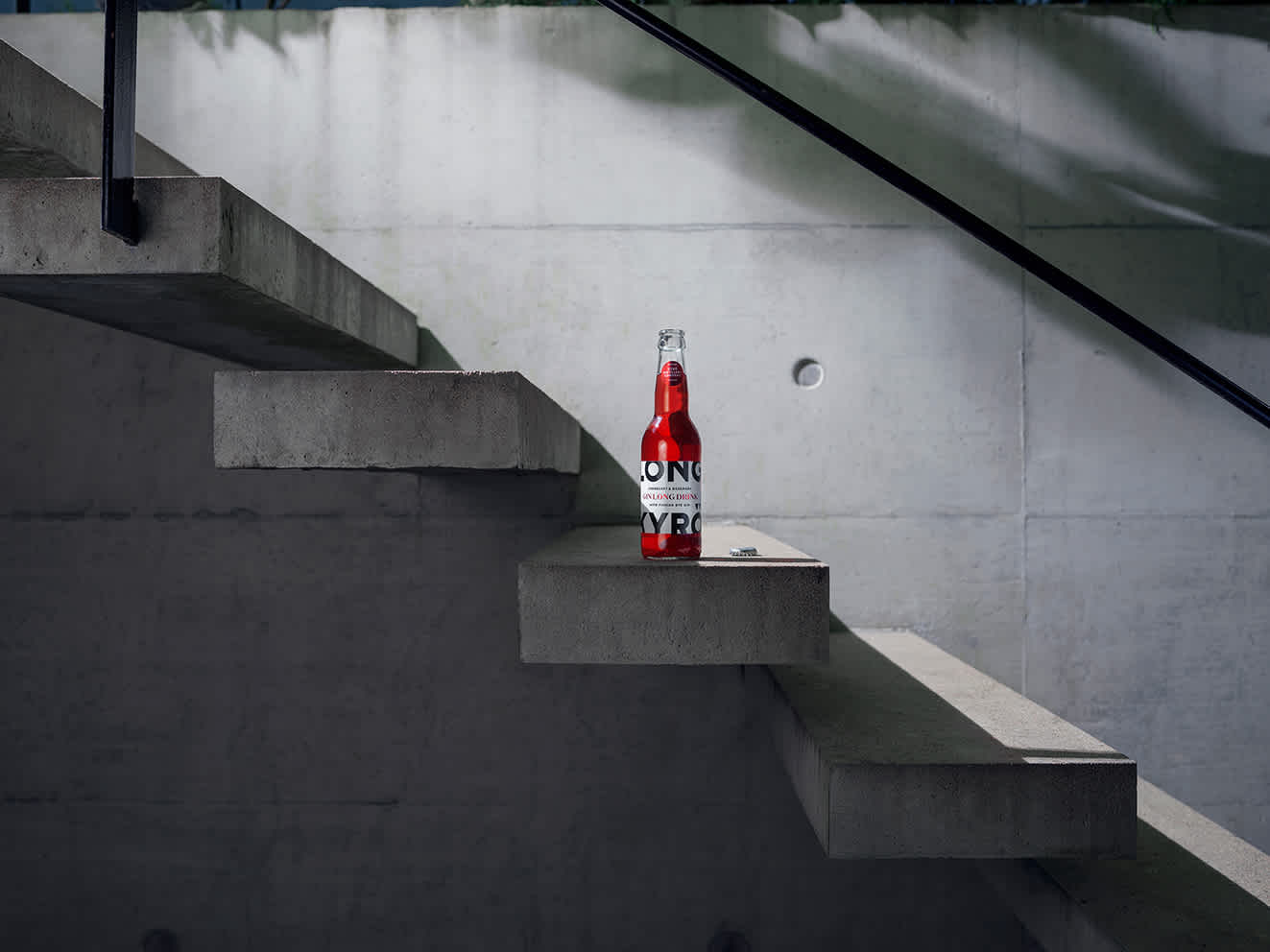 The 330ml vibrant red Kyrö cranberry Longkyrö drink stands on a grey, concrete staircase.
