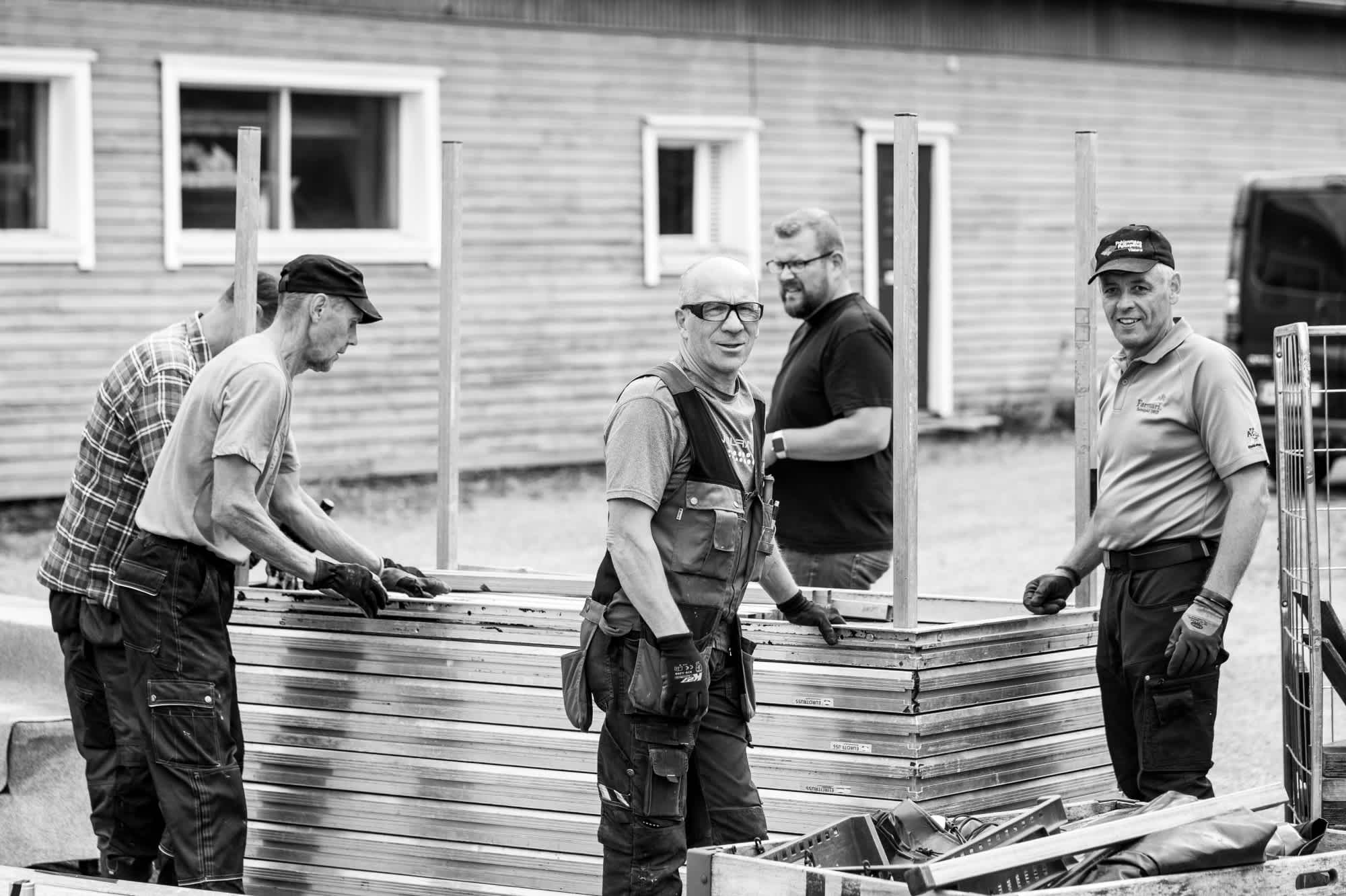 Black and white image of a group of construction workers building something.