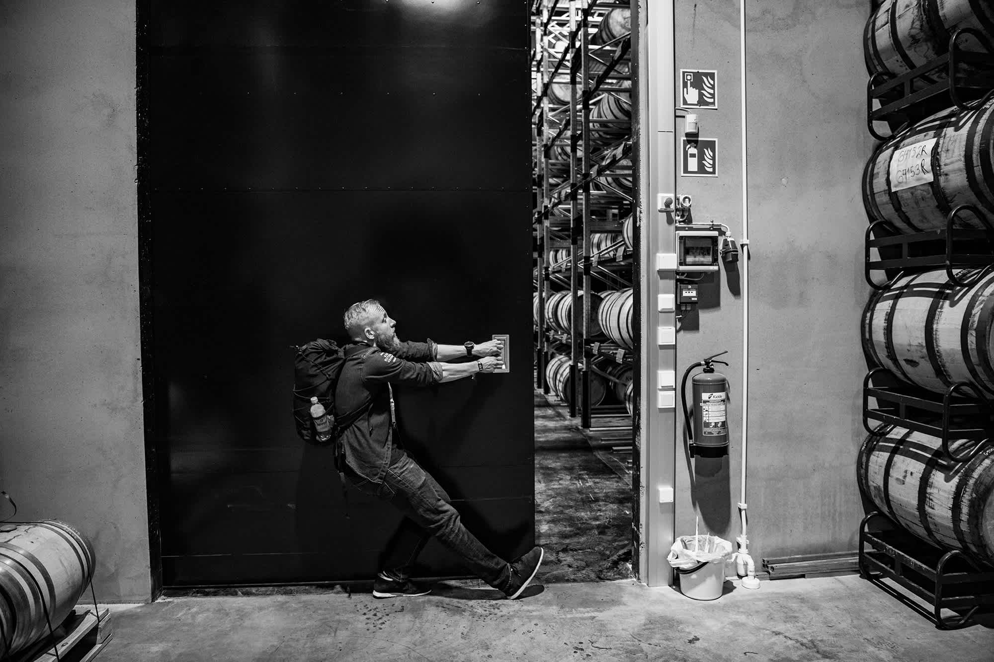 Black and white image of co-founder Mikko Koskinen opening a door in the whisky barrel warehouse.