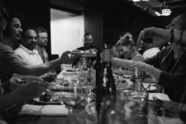 Black and white image of a group of people sat across each other on a long, communal table sharing plates and enjoying good drinks.