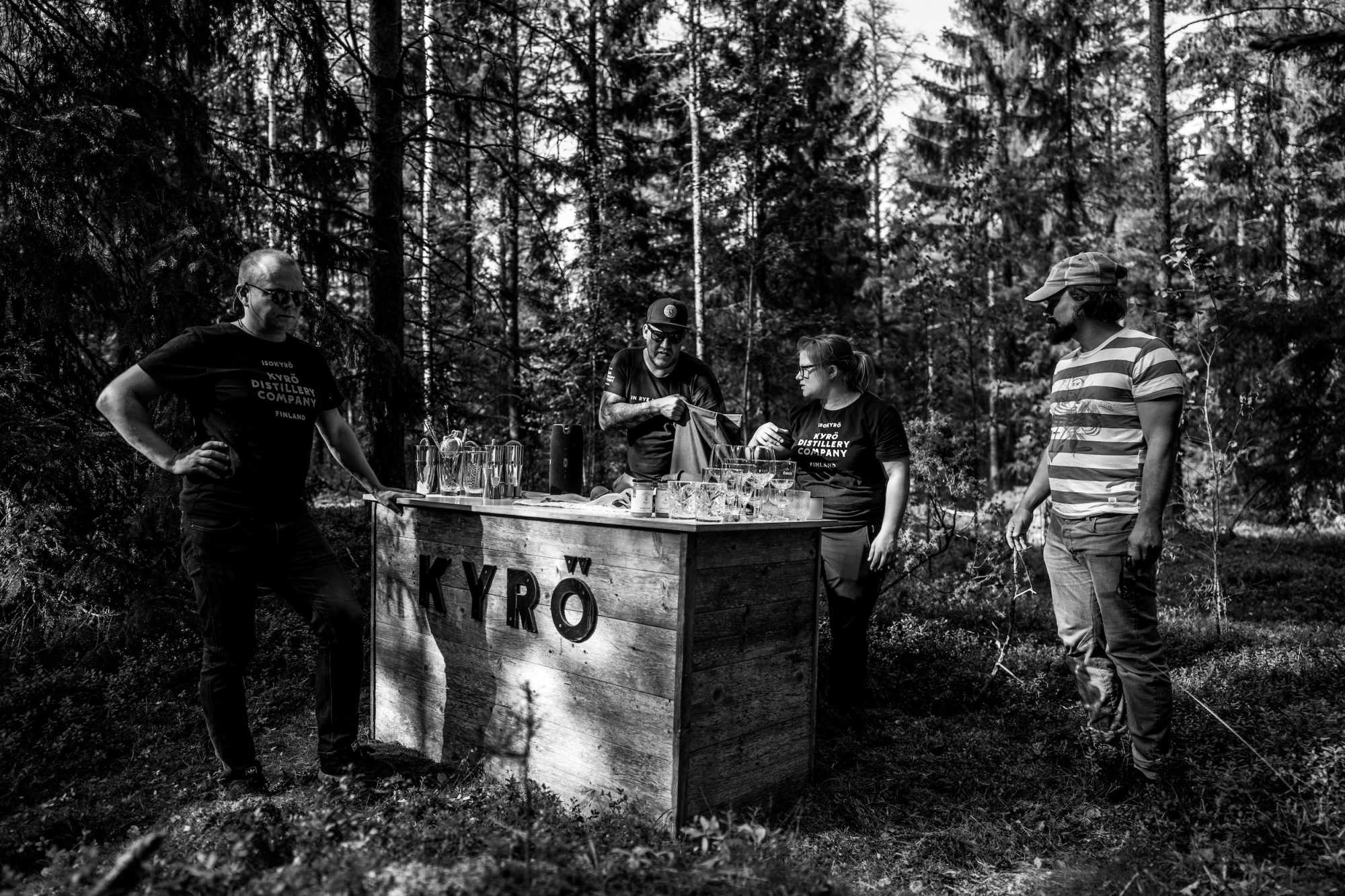 People standing in the middle of the forest next to a bar set-up with Kyrö bottles and cocktails glasses.