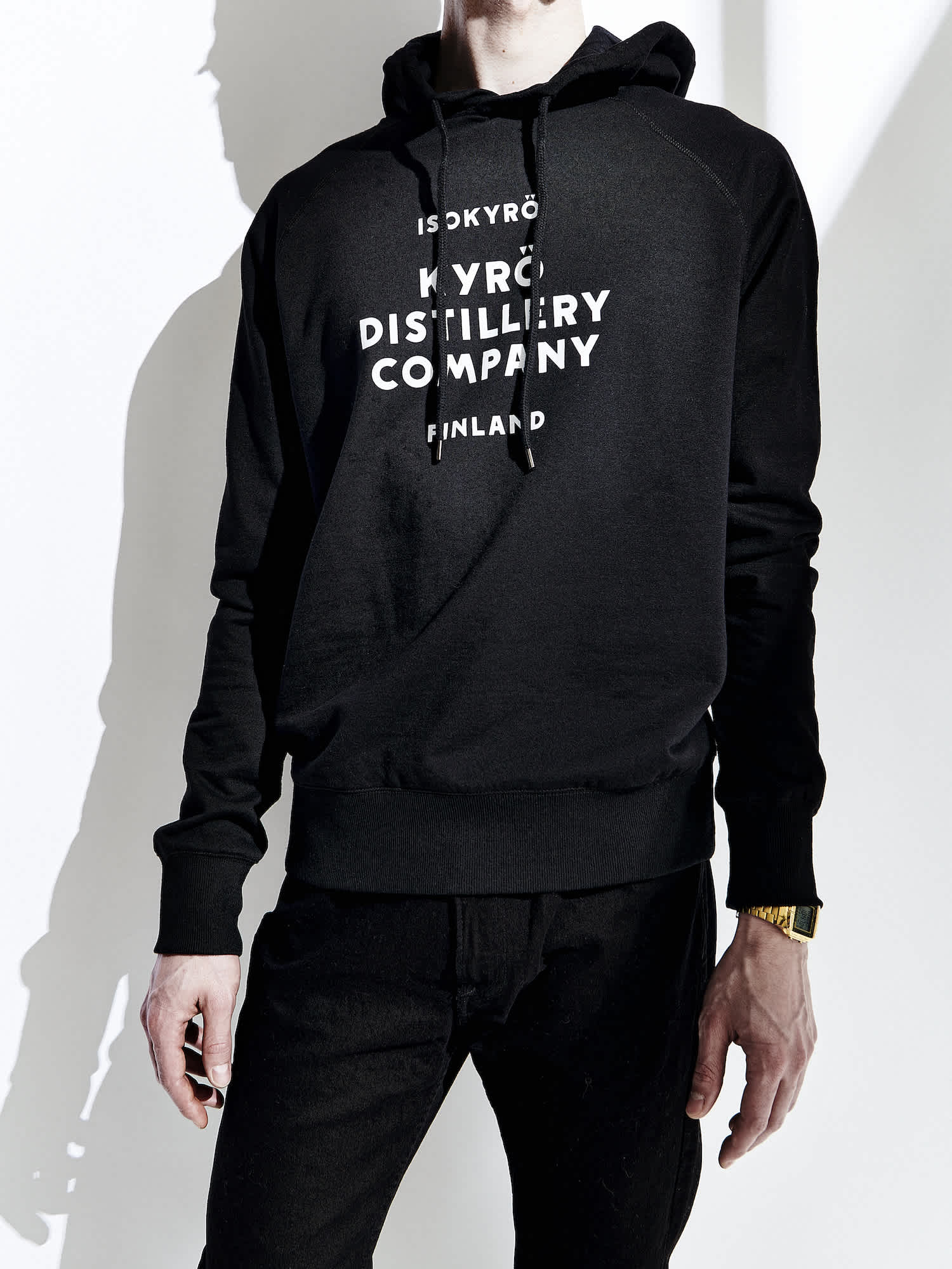 A white, male model wearing a black sweater. The Kyrö logo is displayed in white across the chest.