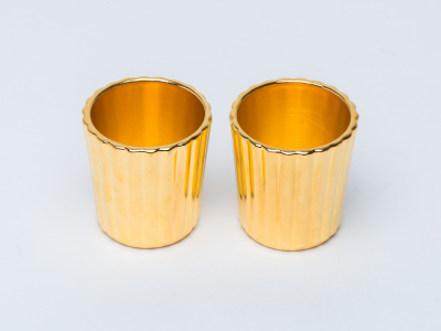 Two gold plated cups standing on a table
