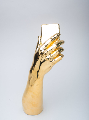 Metal plated gold hand holding an iphone