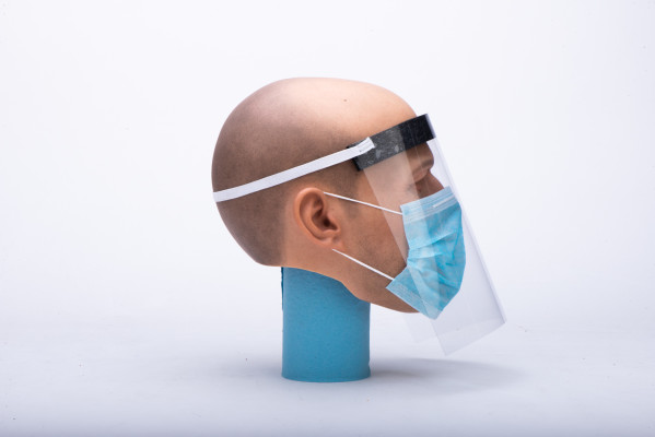 A mannequin wearing a face shield and surgical mask side view