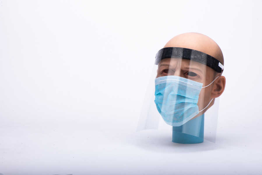 A mannequin wearing a homemade face shield and surgical mask