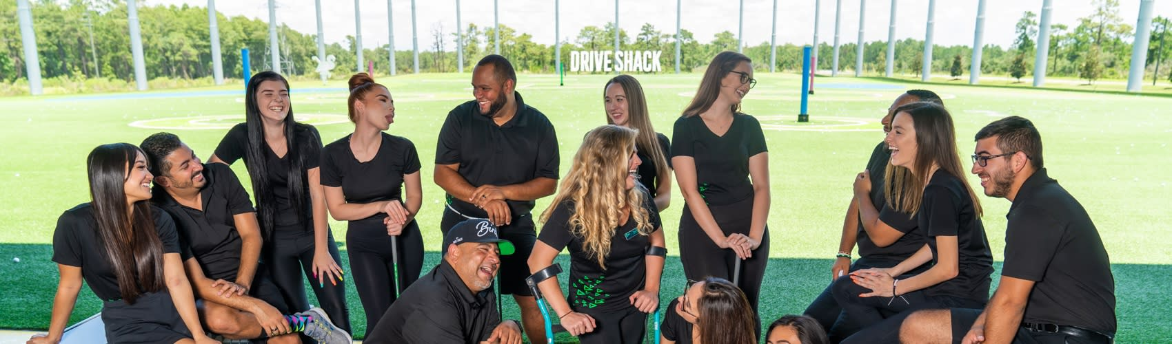 Drive Shack employees in a group laughing.