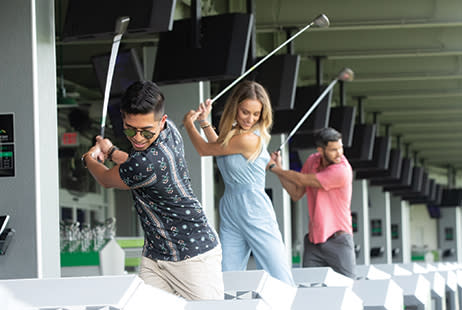 Image of two men and a woman swinging golf clubs at Drive Shack.
