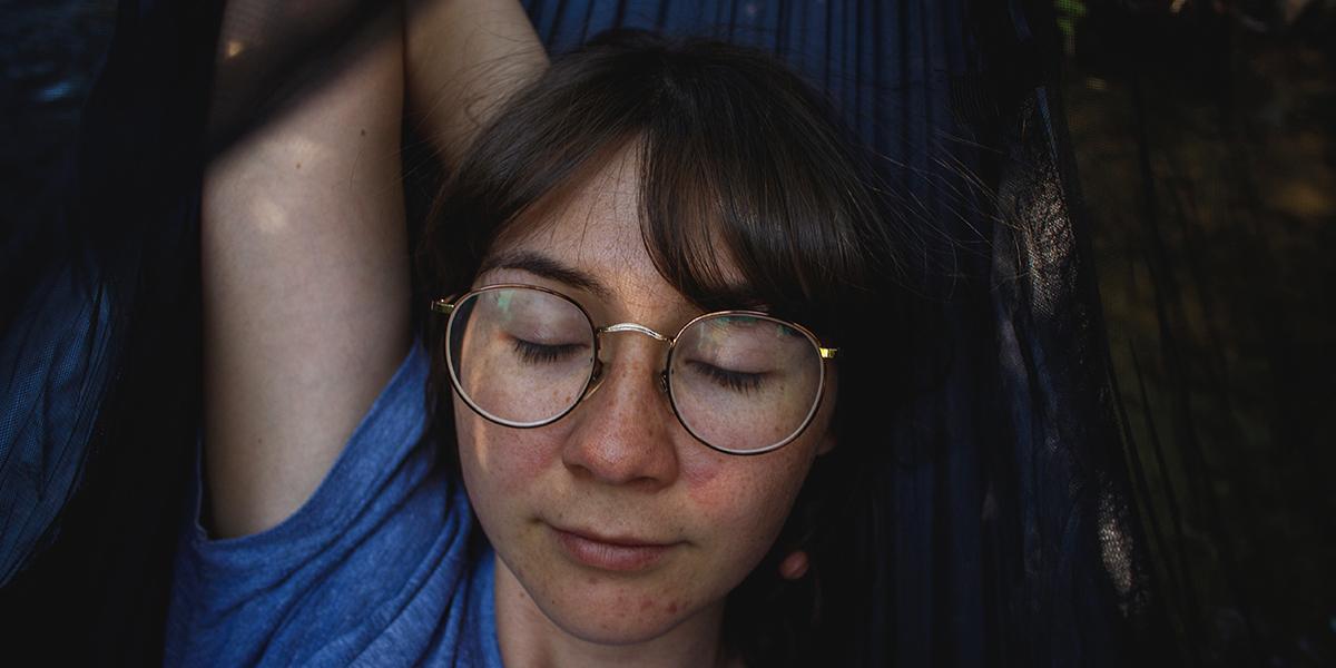 Girl relaxing on hammock, eyes closed