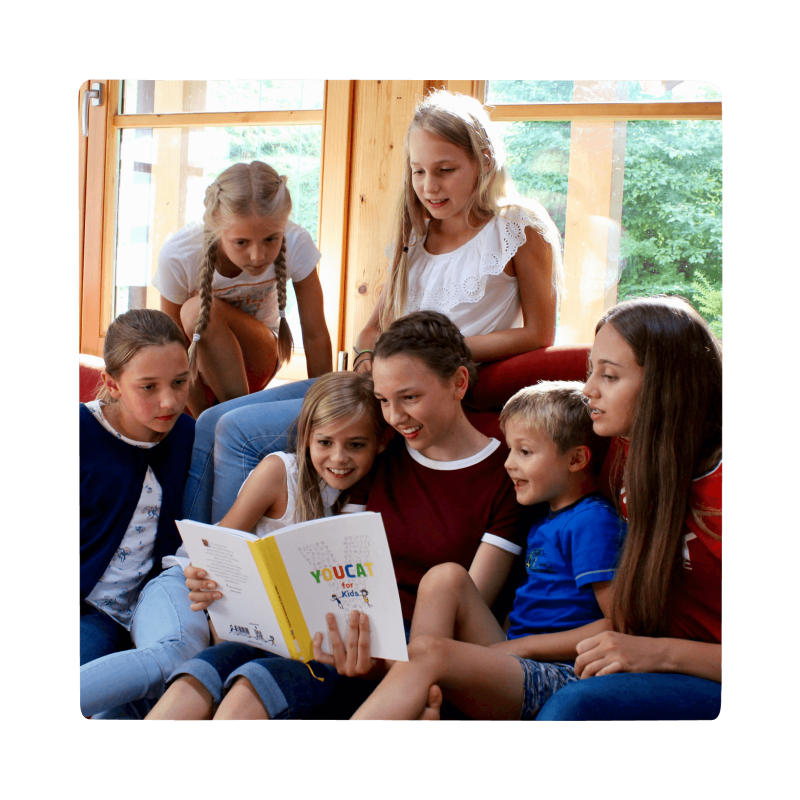 group of children reading youcat for kids book together