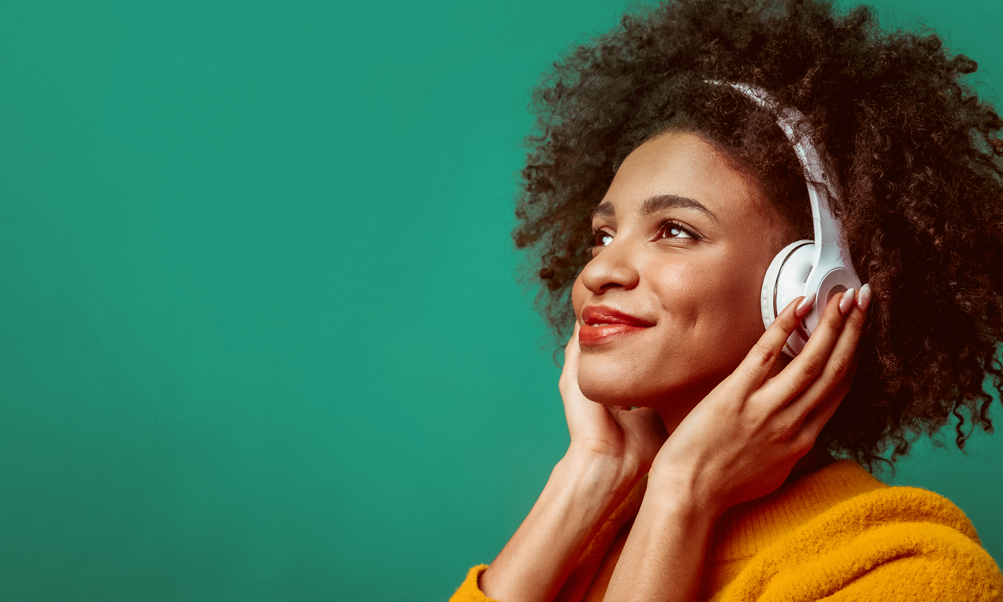Smiling girl with headphones listening to podcasts