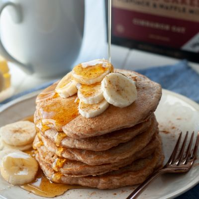 kodiak pancakes stacked on a plate with bananas on top