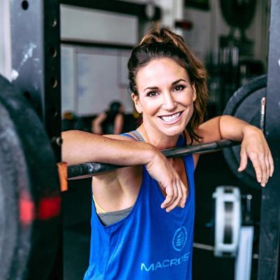 lindsey resting on a barbell smiling