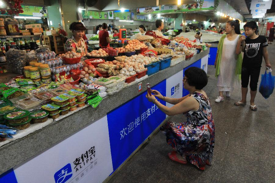A woman crouches and scans a QR code in front of a stand selling fruits and vegetables.