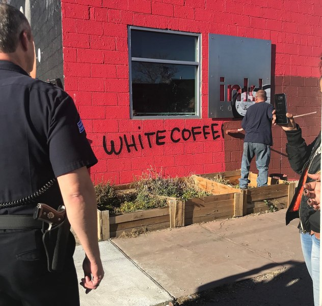 "A person paints over graffiti ""white coffee"" painted on side of a red building while cop watches."
