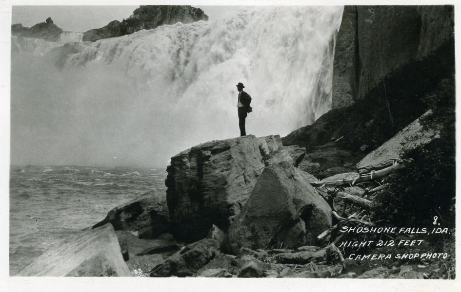 A man stands on a large rock near a waterfall.