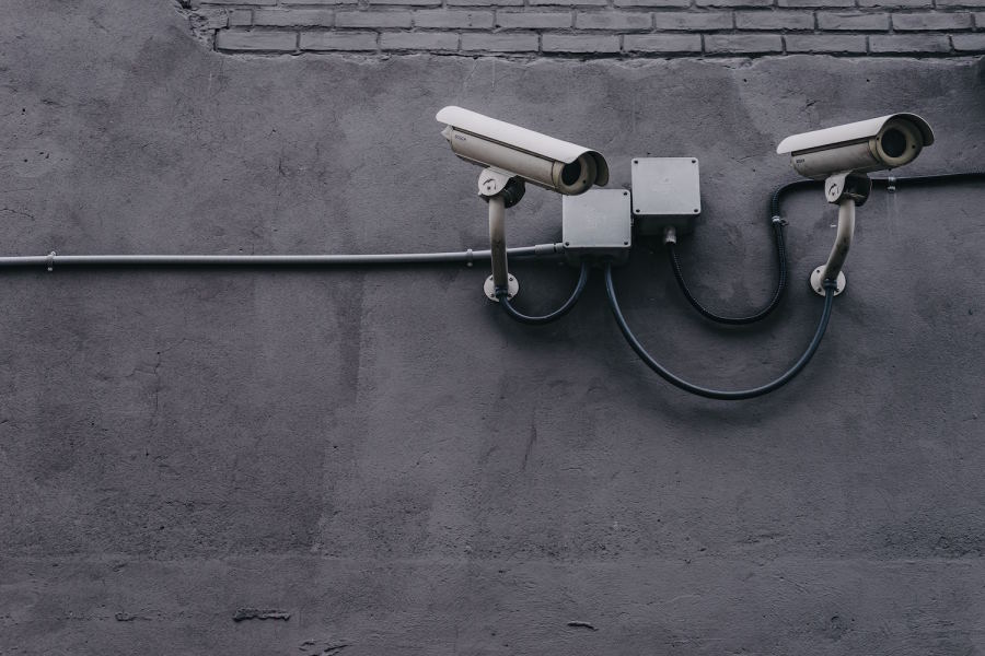 A photo of two security cameras attached to a wall.