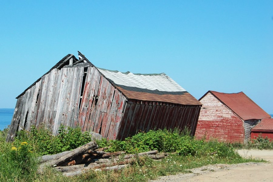 A photo of two small wooden buildings, one of which is dilapidated.