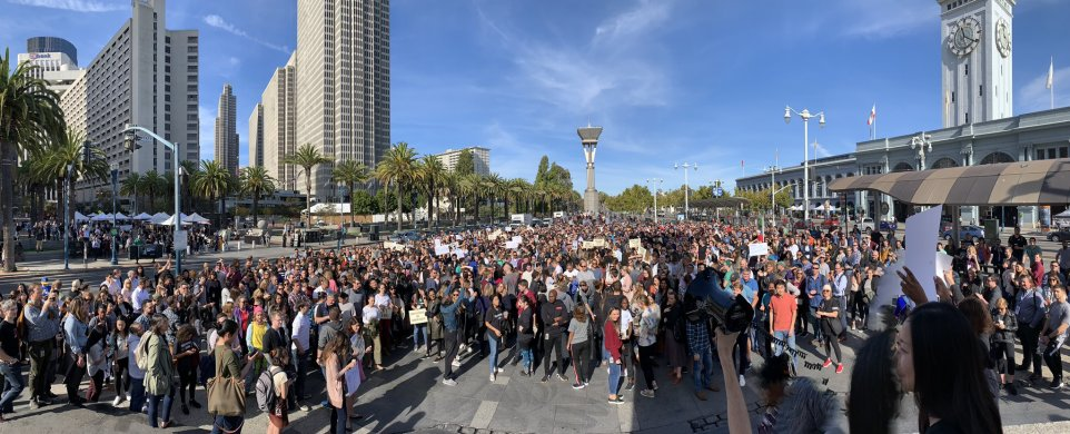 A crowd of hundreds of people in front of San Francisco's Ferry Building.