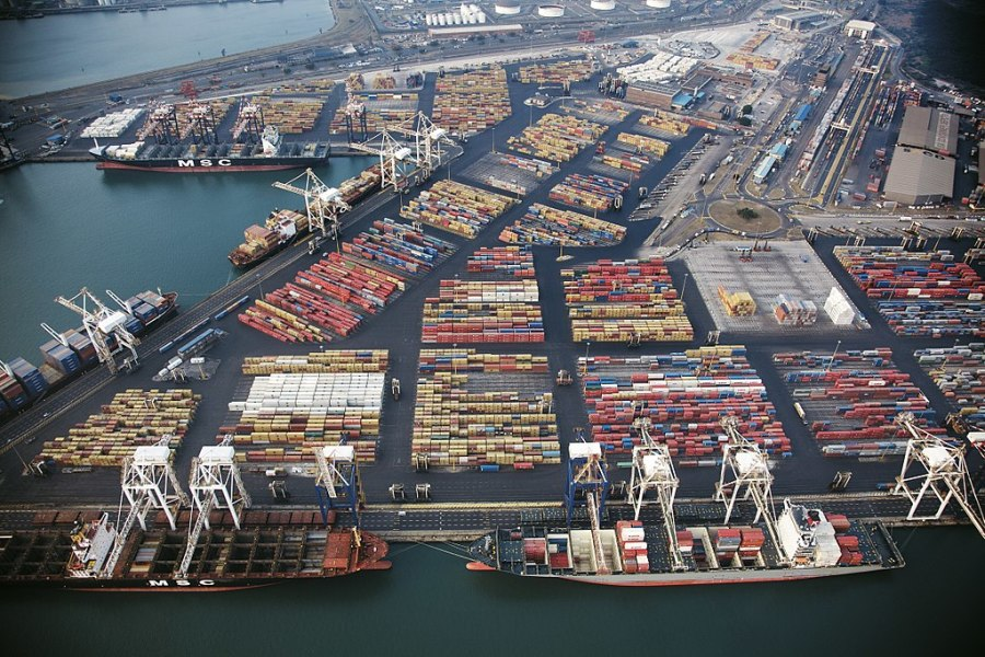 A port with container ships and neatly organized, colorful containers.