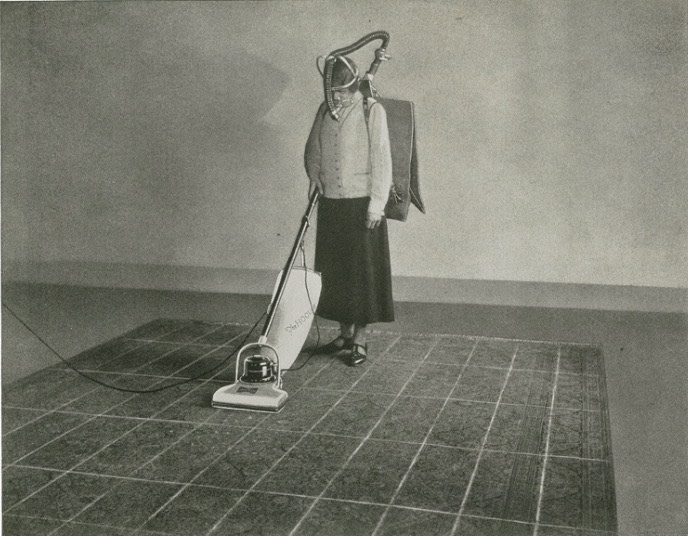 A woman uses a vacuum cleaner.