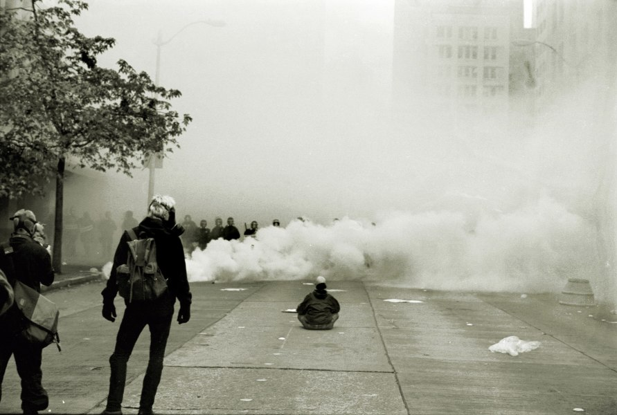 A photo of a few protesters facing a line of riot police and a cloud of tear gas.
