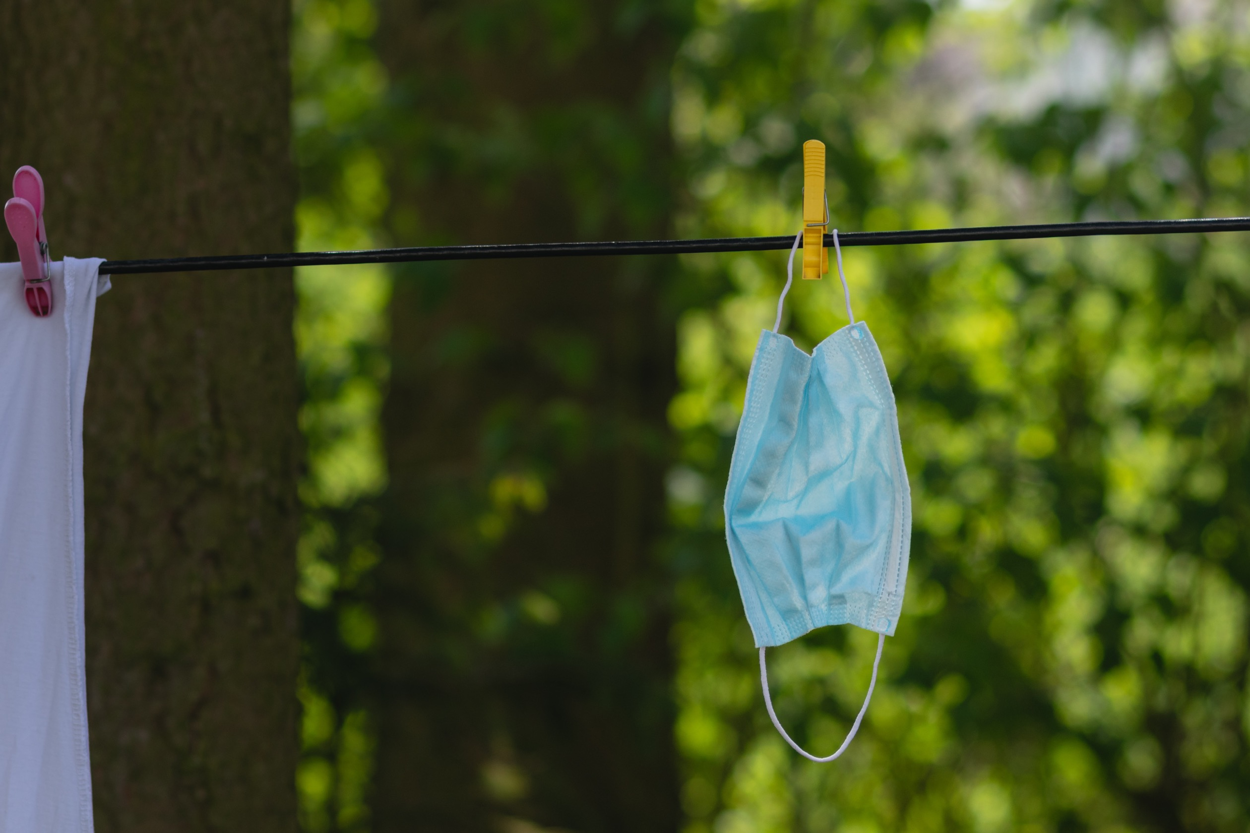 A surgical mask hanging from a clothesline outdoors.