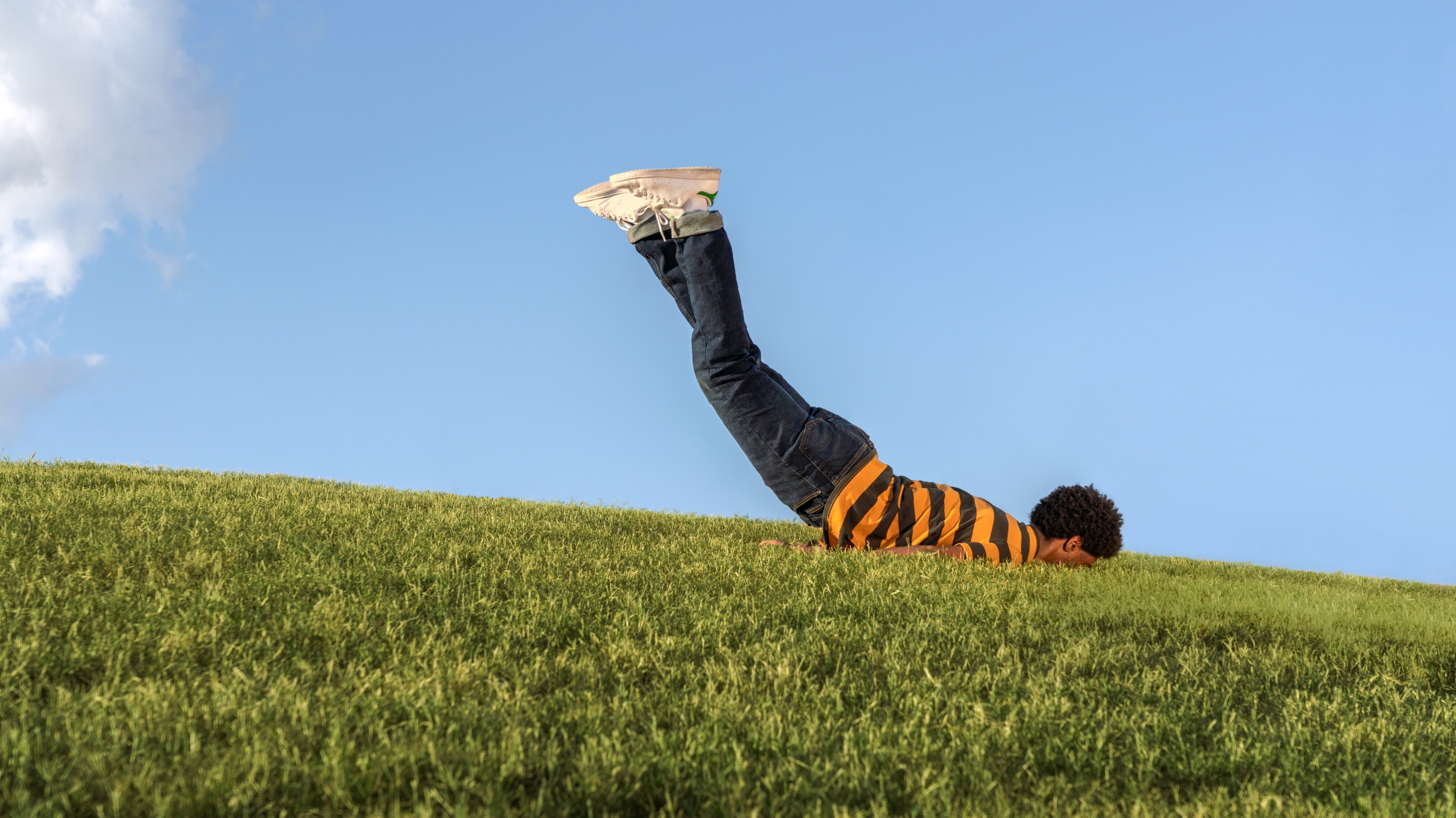 Man facedown on a grassy field in springtime.