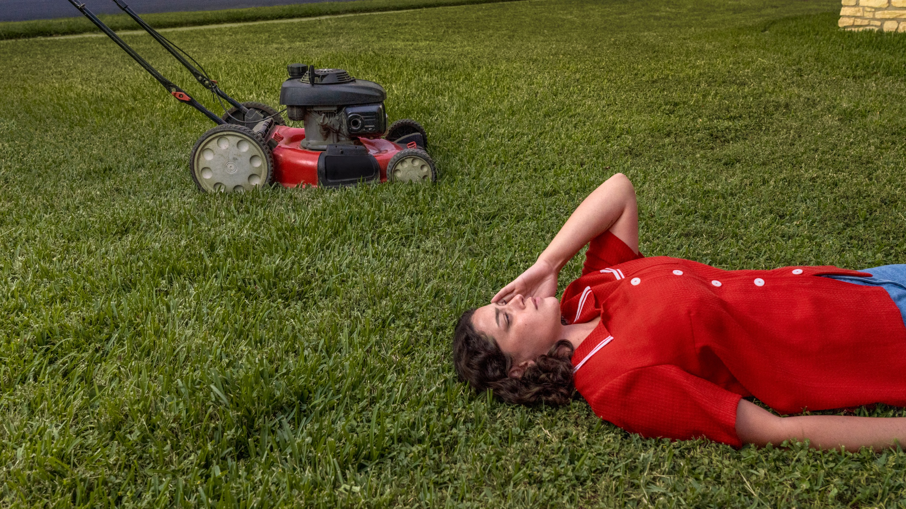 A person lying in the grass holding their head while a lawnmower goes by in the background.