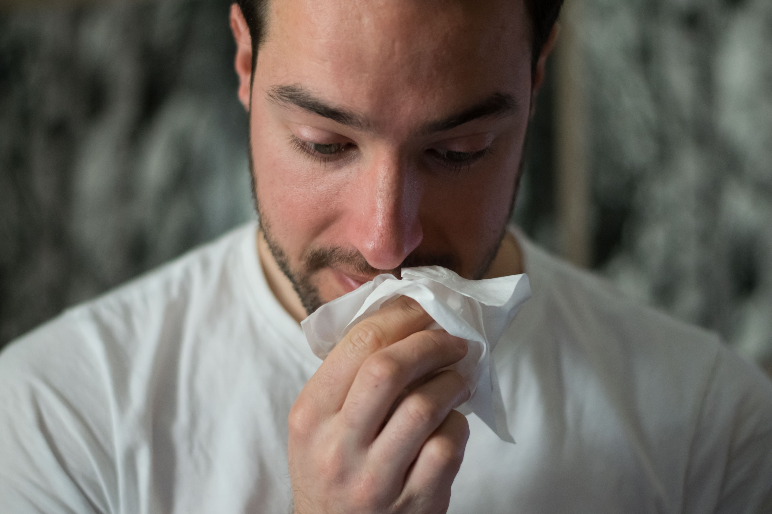 A man holding a tissue to his face while looking downward.