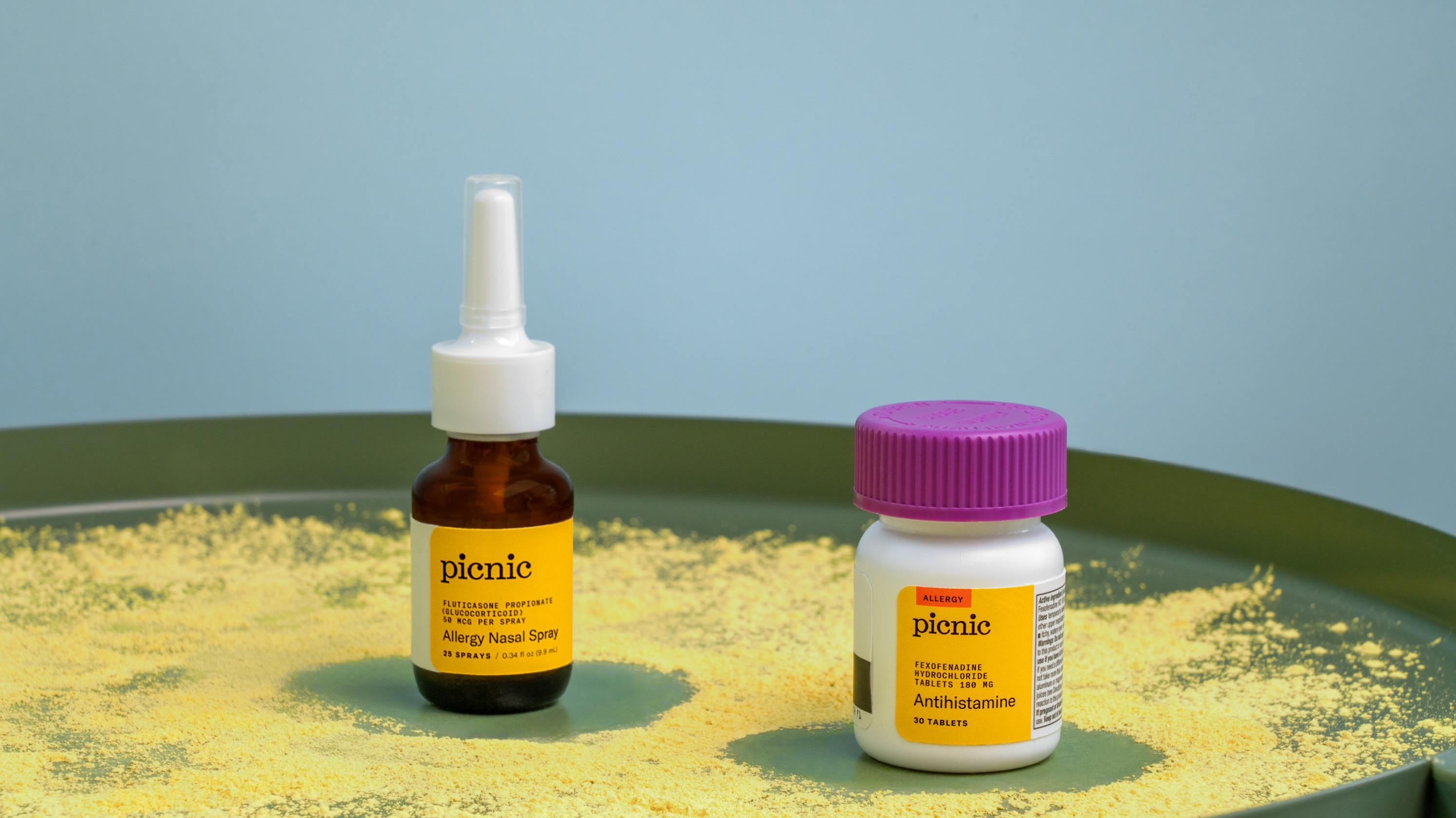 Picnic's over-the-counter nasal spray and a bottle of antihistamines on a tray sprinkled with pollen.