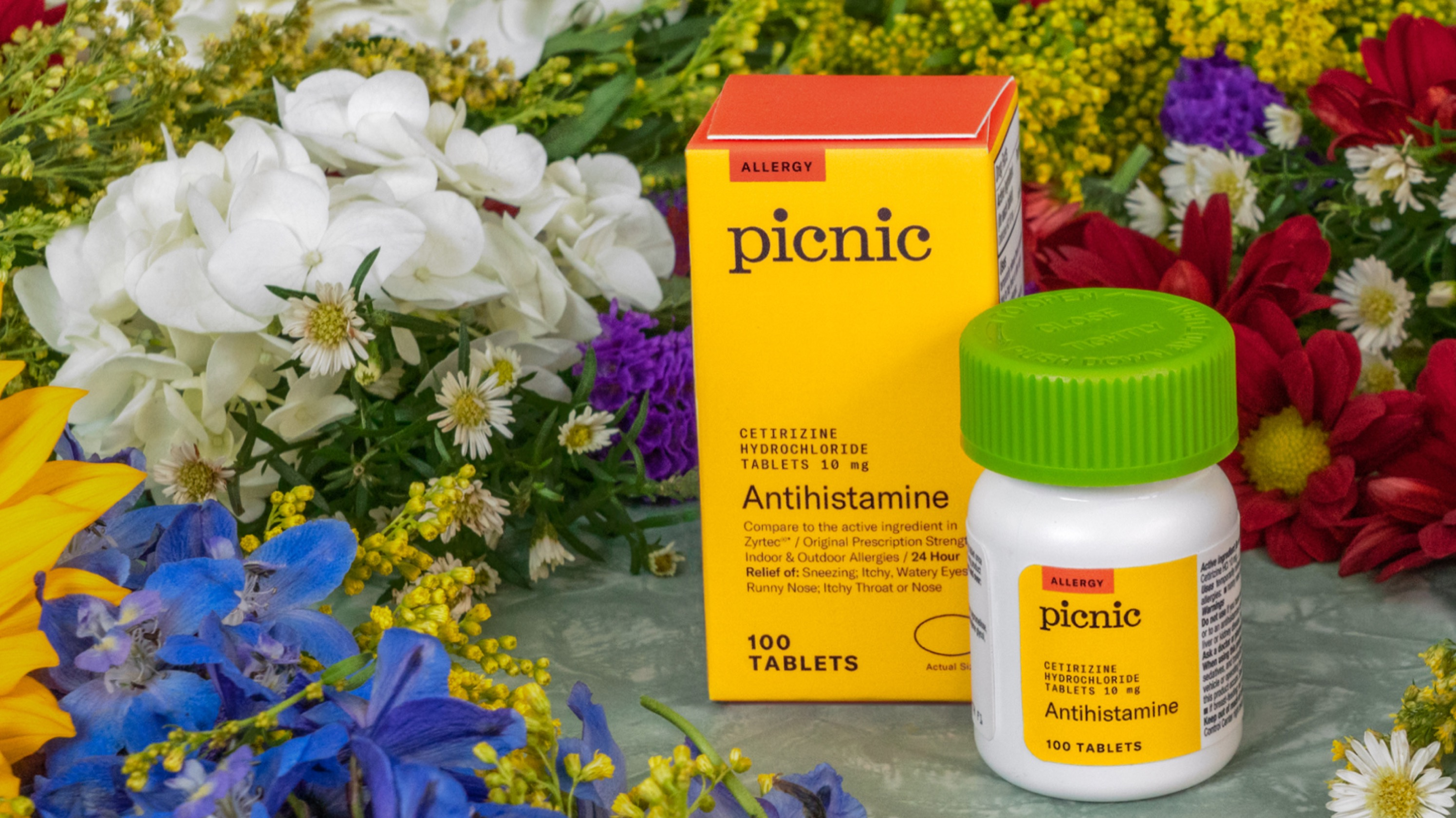 Picnic's over-the-counter antihistamine surrounded by flowers.