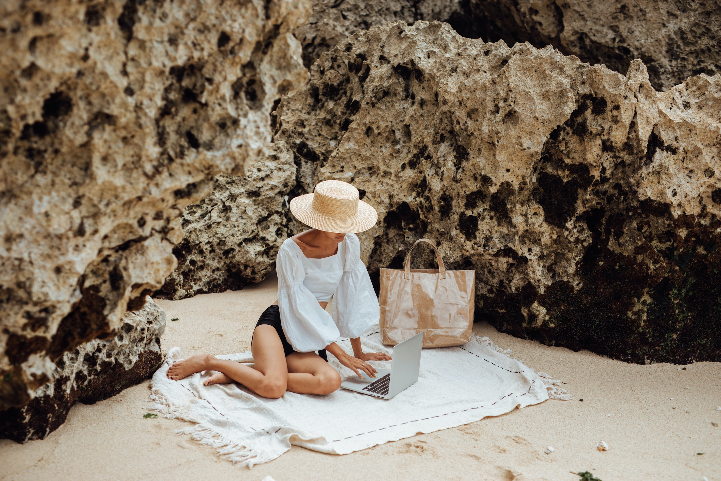 Image of a person reading on their laptop while relaxing at a beach.
