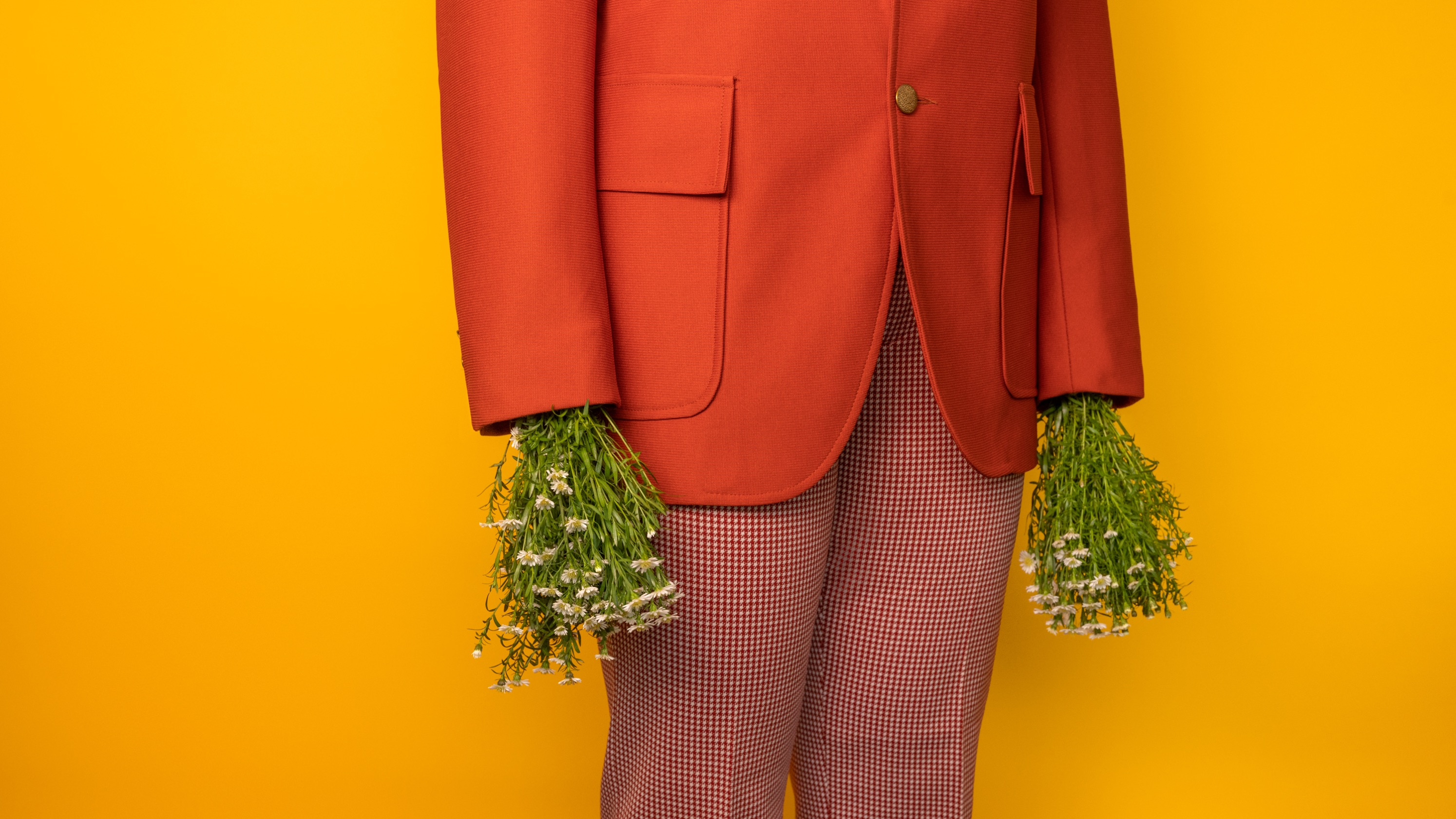 Close-up of a person's torso wearing a brightly-colored suit. Instead of hands, bushels of flowers stick out of the sleeves.