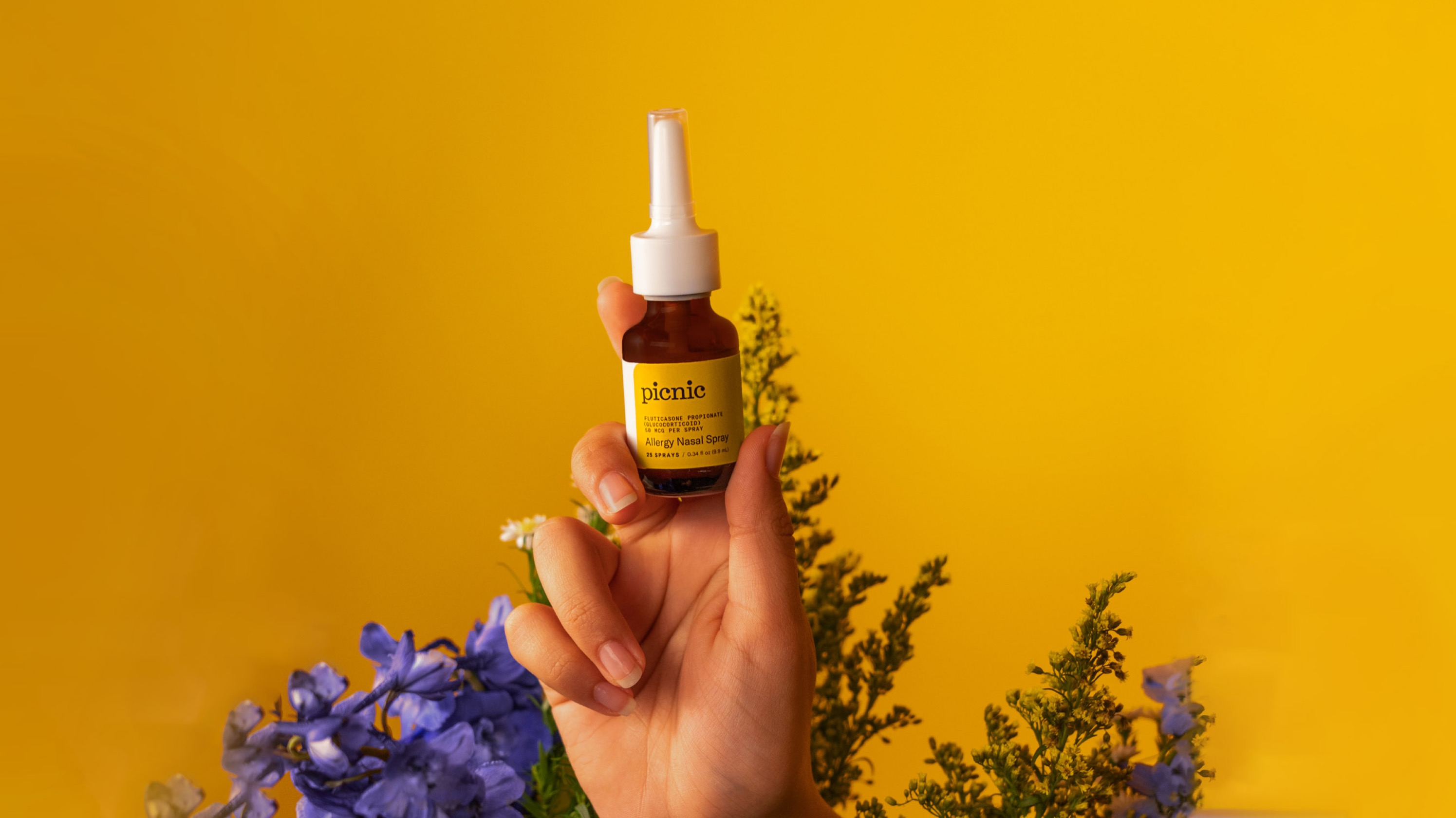 A person's hand holding up Picnic's nasal spray in front of flowers.