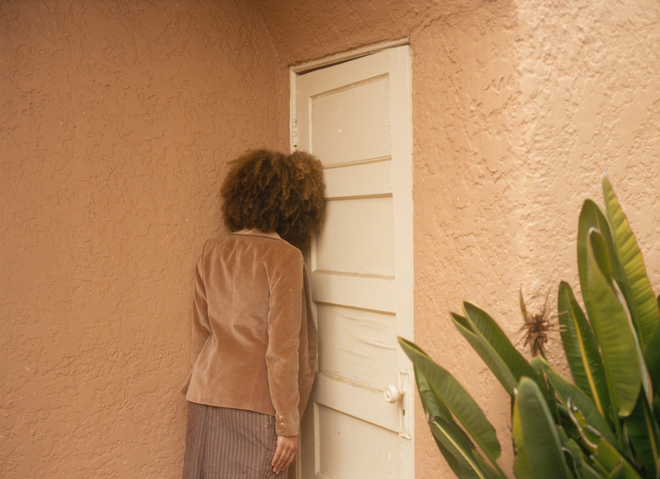 A person facing away from the camera leaning their head against a door in frustration or sadness.