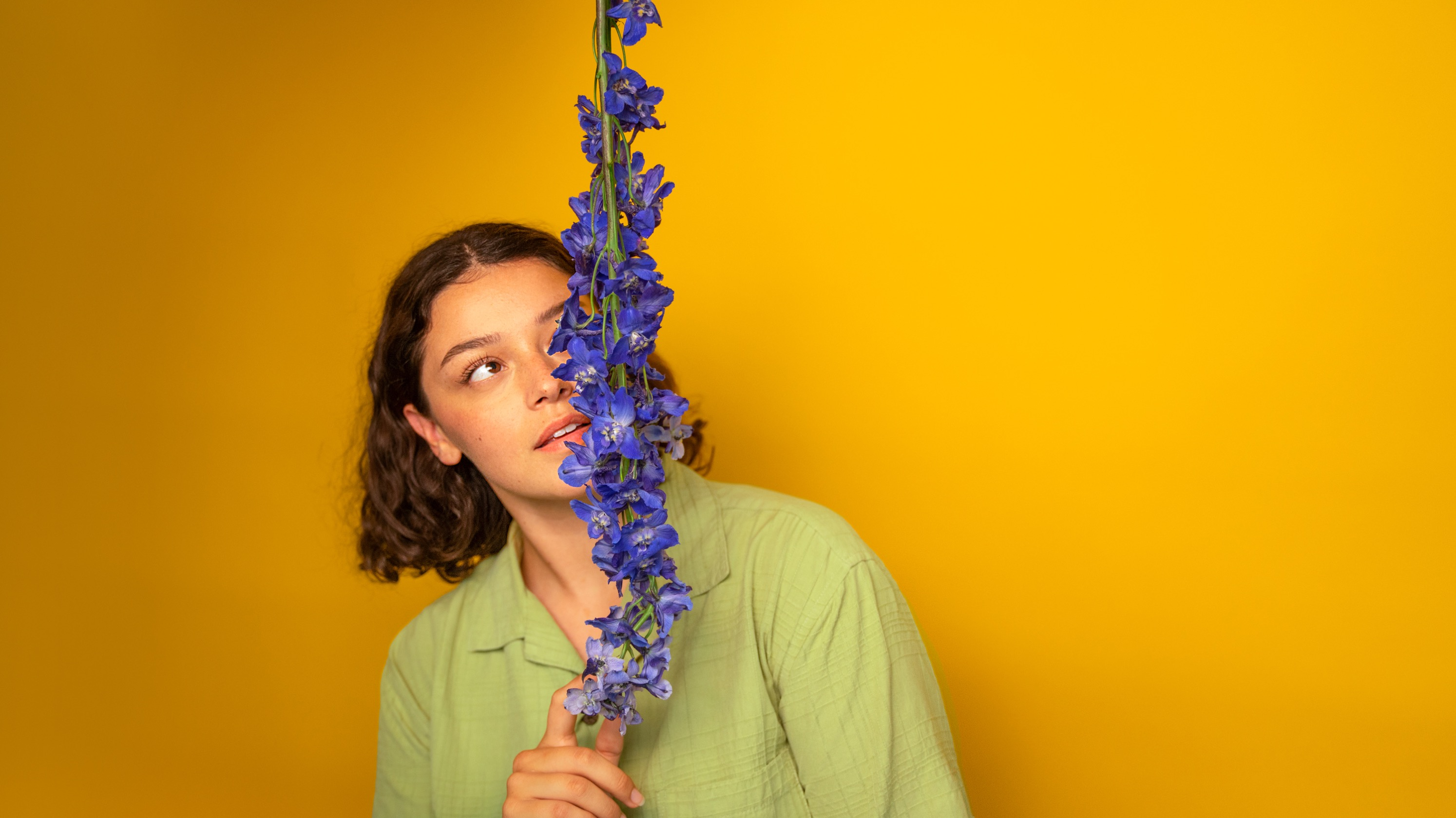Woman standing in front of a yellow background looking at a vine covered in purple flowers.