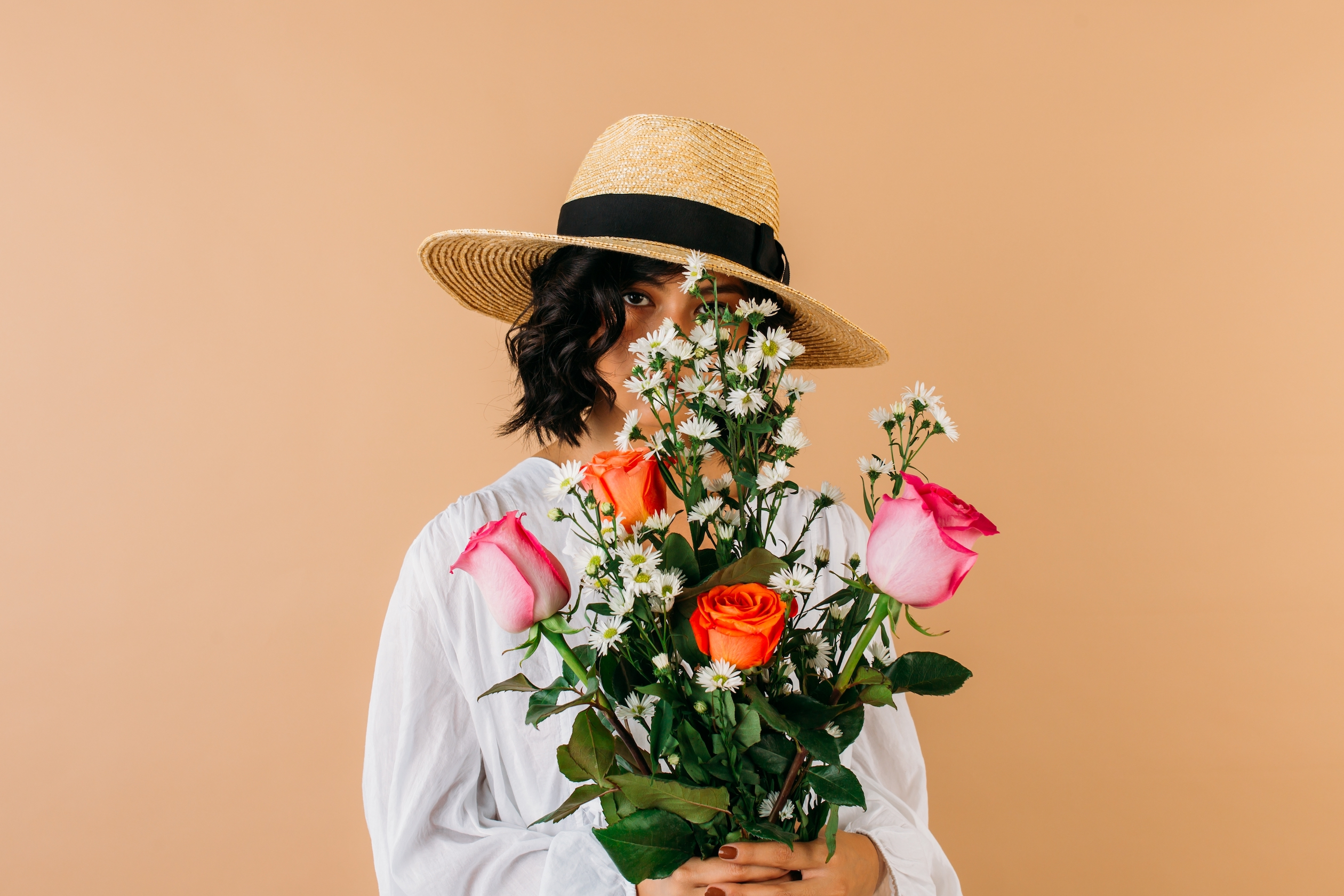 Image of a woman wearing a sunhat holding a bouquet of flowers.