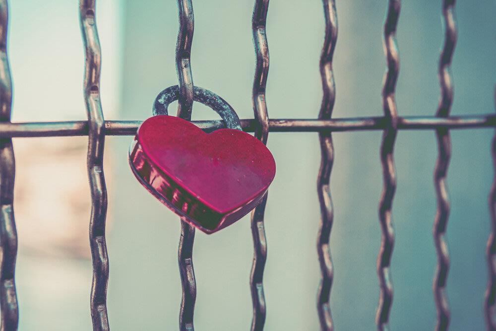 A love heart padlock locked to a fence.