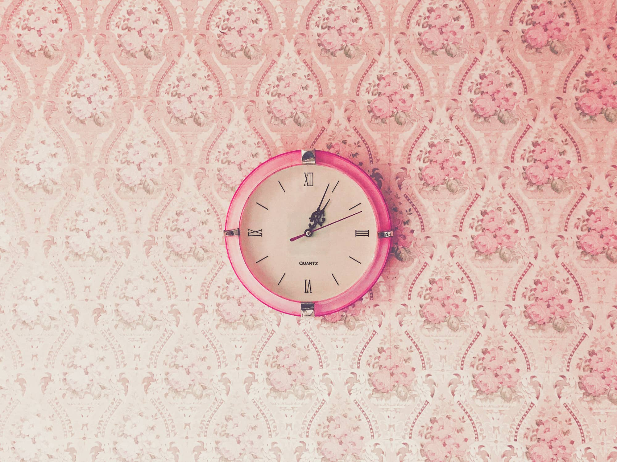 A pink clock with roman numerals hanging on a wall of garish wallpaper.