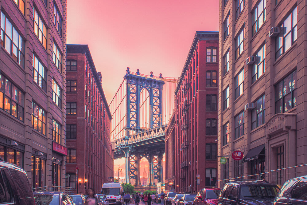 An urban street with a view of a suspension bridge at the end.