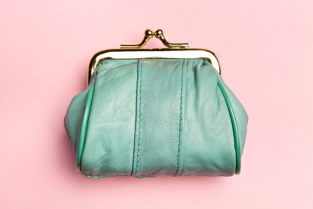 A green leather purse on a pink background