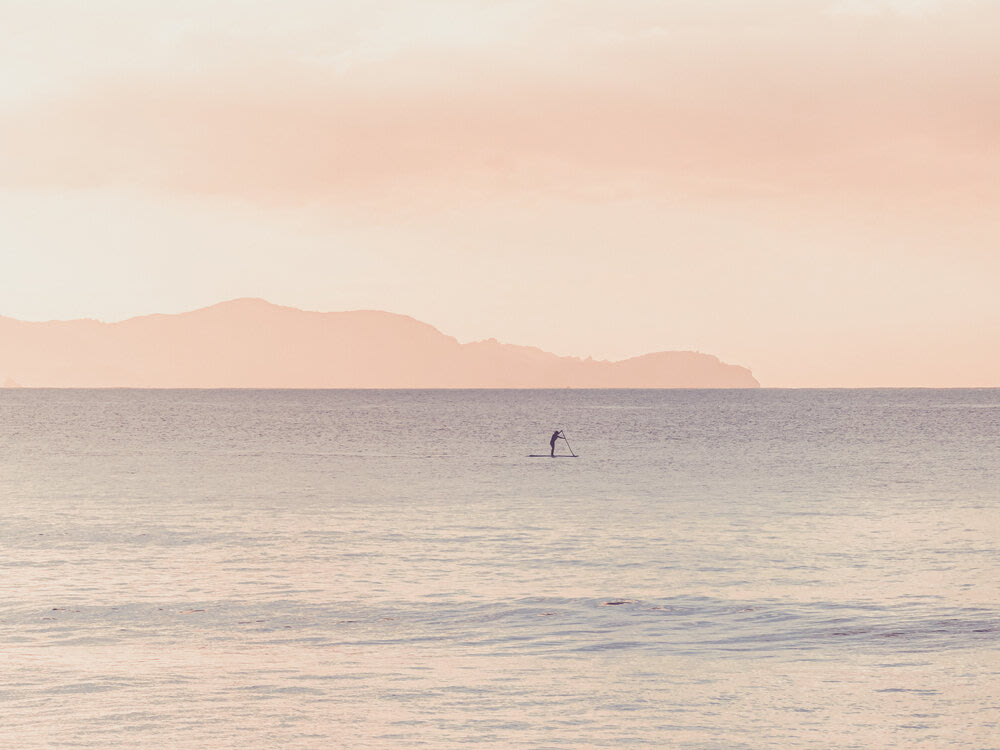 Ocean with lone stand-up paddle boarder in the distance.