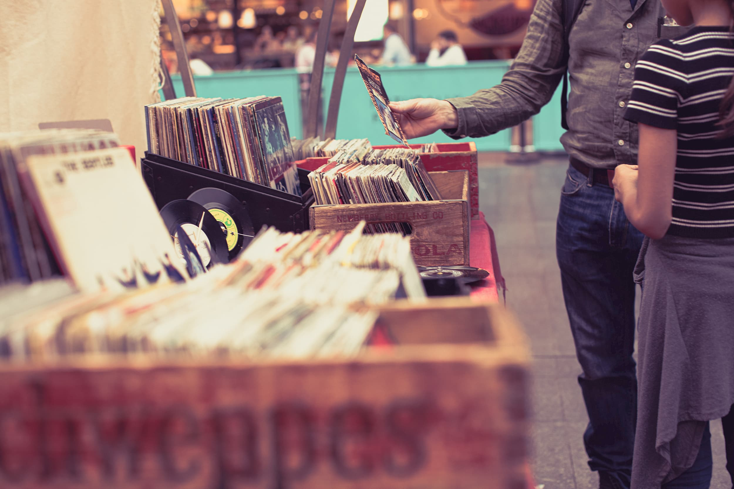 A man picks up a vinyl record from a box on a table.