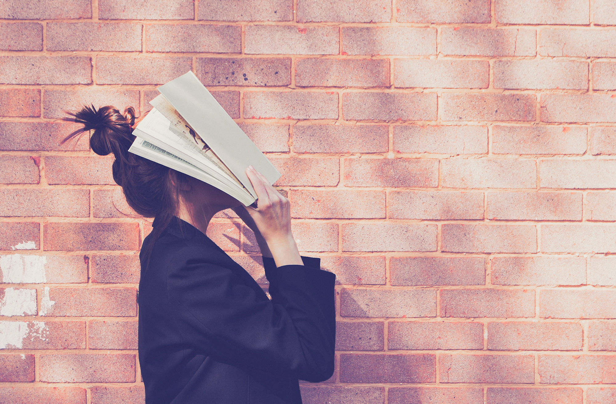 A woman standing in profile with a book spread over her face.